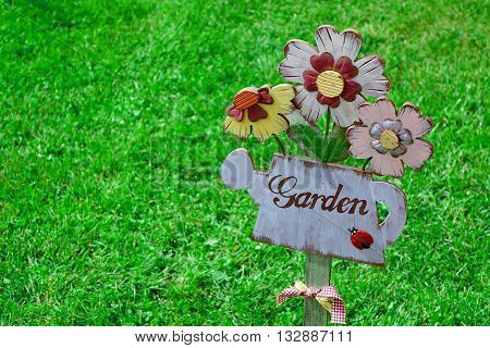 Close-Up Of Wooden Plaque In The Shape Of A Watering Can And Garden Sign. Backyard Garden Lawn In The Background