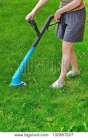 Young White Woman Holding A Corded Grass Trimmer On The Backyard Lawn At Summertime