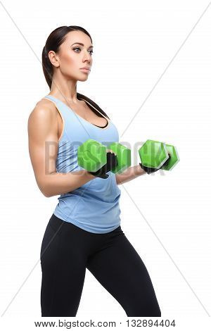 Beautiful sporty woman in sportwear making exercise with green dumbbells. Isolated over white background. Copy space.