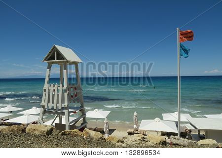 Lifeguard tower with lifeguard flag on a Greek beach. A lifeguard tower with a relevant flag saying