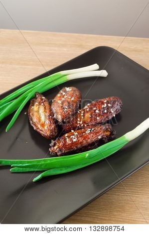 Chicken wings in soy sauce on a black plate