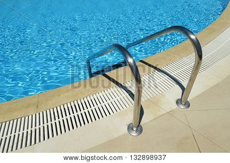 Outdoor swimming pool ladder. Grab bars metal ladder to a blue water pool.