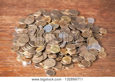 Money coin spare change pile dark wood background concept.