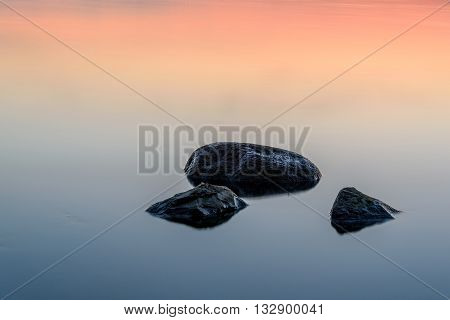 Beautiful abstract pink and blue decorative background with a smooth surface of the water and stones at sunset taken on a long exposure