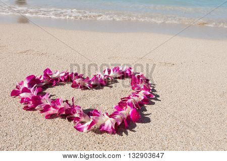 orchid flower garland necklace in love heart shape on white sea sand beach, romantic couple honeymoon trip at Hawaii