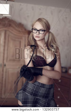 Sexy naked blonde woman in glasses with whip indoor bdsm