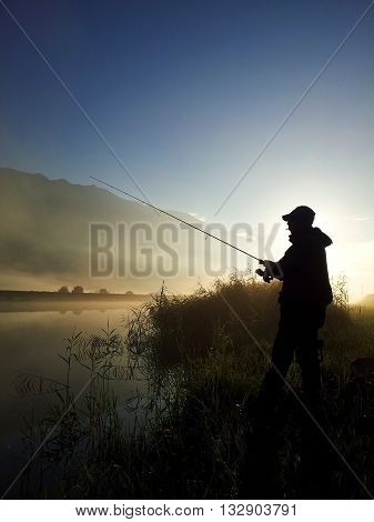 shot of Silhouette of Fisherman at sunrise