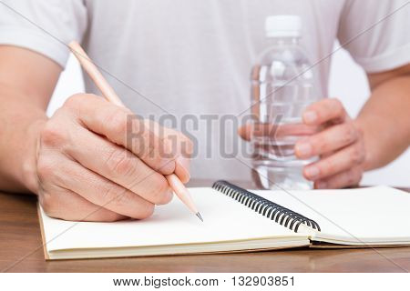 Close up of businessman's hand holding a pencil to write on an empty notebook and holding bottle of water on another hand selective focus on the hand with pencil