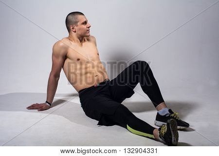 Muscular man sitting naked torso. Athletic young man in sweat pants and sneakers