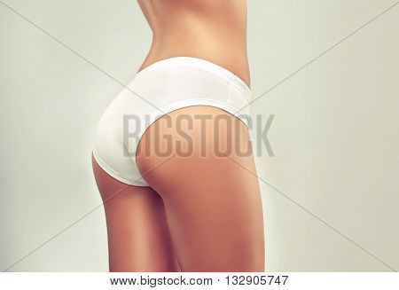 Slim tanned woman   Perfect Body  .Taut elastic ass . Firm buttocks .  Slim toned young body of the girl . An example for sports and fitness or plastic surgery and aesthetic cosmetology