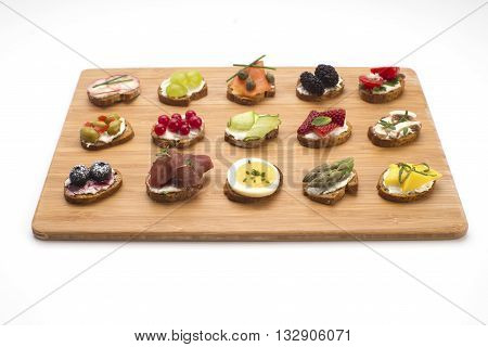 Bite size canapes on a wooden serving board. Party food crackers with different toppings isolated on white.