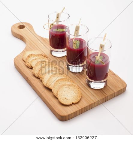 Cheese and beetroot sauce snacks in shot glasses served on a wooden board. Party food isolated on white.