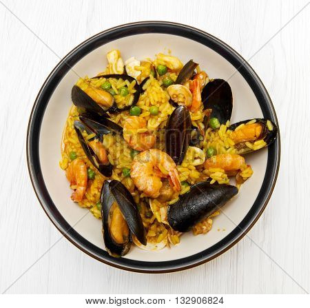 dish with paella and seafood on white wooden background