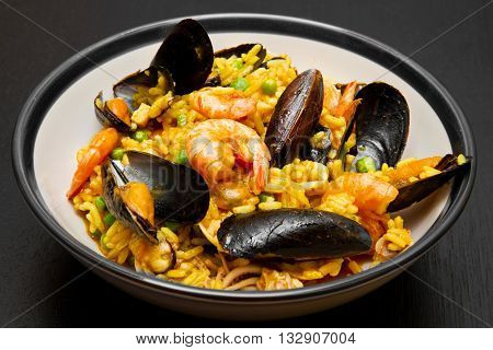 dish with paella and seafood on black background