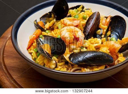 dish with paella and seafood on wooden background