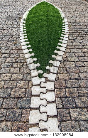 Artistic sidewalk zip reveals green grass for an environmental concept.
