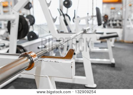 Empty barbell grip on its training device. Side view on training device with barbell grip at gym interior. Close-up of training device with barbell.