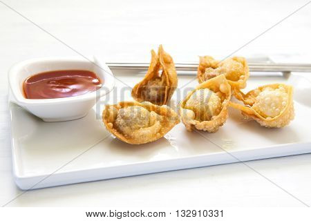 deep fried won ton with sweet and sour sauce on tray