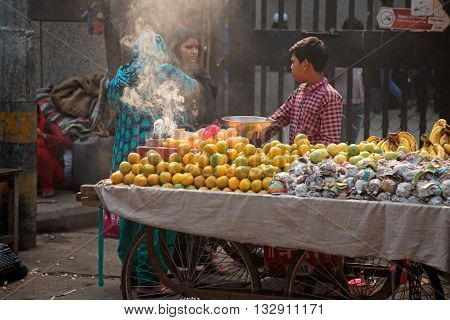 DELHI, INDIA - NOVEMBER 20, 2015: An Indian boy selling his fresh produce on a crowded street market of Old Deli