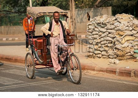 DELHI, INDIA - NOVEMBER 20, 2015: Indian man sitting on a cycle rickshaw waiting for people to transport