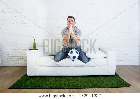 football fan watching television soccer match suffering stress nervous and excited praying god on home sofa couch holding ball in grass carpet emulating stadium pitch looking anxious