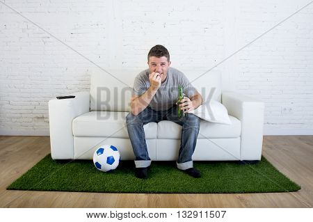 crazy football fan cheering watching television soccer match suffering stress nervous and excited biting his fingernails sitting on sofa couch with grass carpet and ball emulating stadium pitch