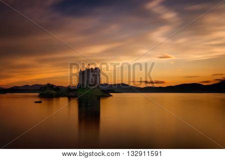 Stalker Castle reflection in orange sunset light Highlands Scotland
