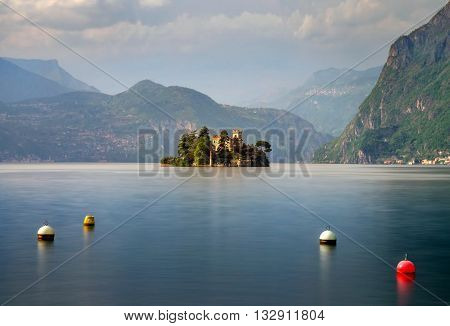 Little island Isola di Loreto on Iseo Lake and four buoys Italy
