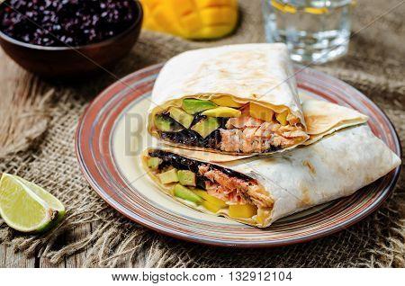 Salmon avocado mango black rice burritos on wooden background