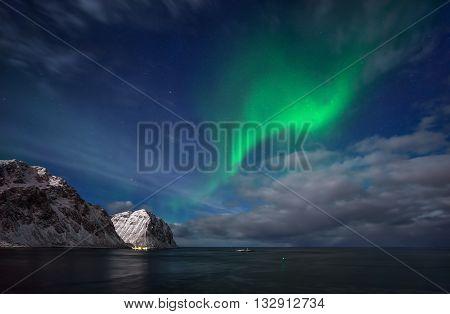 Aurora above Flaget bay and mountains Lofoten