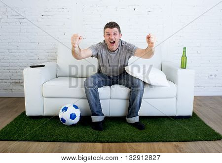 crazy football fan cheering happy watching television soccer match celebrating scoring goal excited and euphoric sitting on sofa couch with ball and grass carpet emulating stadium pitch