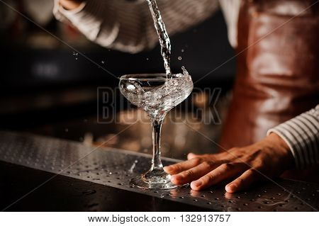 Barman pouring , splashing cocktail into a champagne glass and making a splash. no face