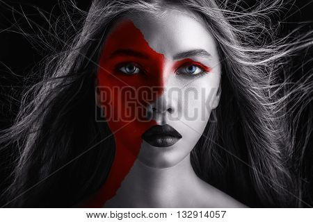 Beautiful young woman with fashion makeup and red paint on his face on a black background