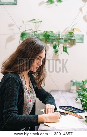 Young female painter drawing with concentration side view. Half face of young pretty artist drawing with serious face. Intently drawing female beautiful young painter.