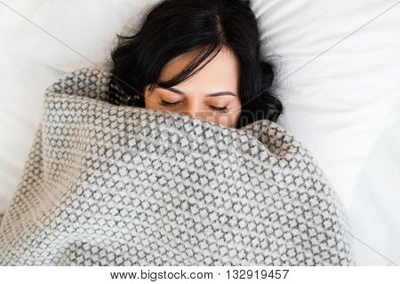 Sleeping woman cover face with blanket flat lay. Close-up of young brunette women, sleeping under gray blanket and covering half face. Almost fully covered sleeping girl