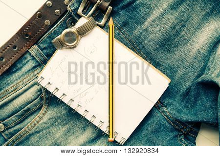 Jeans with wrist watch, notebook and pen
