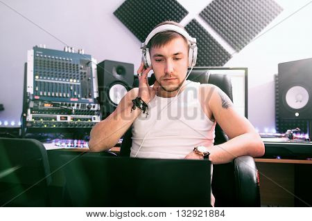 DJ listening music in the  sound recording studio. Sound producer listens music track. Young man listening to headphones in  sound recording studio interior. Concept of writing music