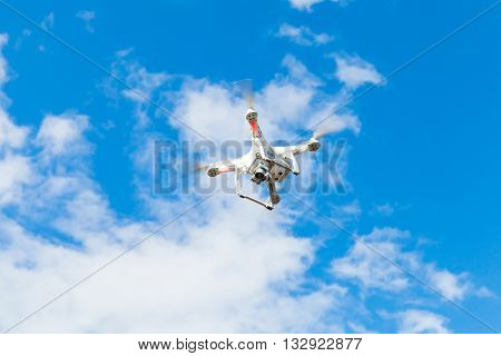 White Quadrocopter Flying In Blue Cloudy Sky, Drone