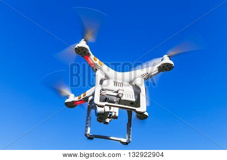 White Quadrocopter Flying In Blue Sky, Closeup Photo
