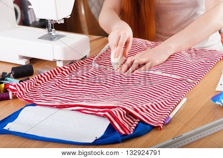 Woman Measuring Pattern On Fabric