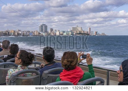 Havana, Cuba - january 19, 2016: Tourists visiting the Malecon in an open bus