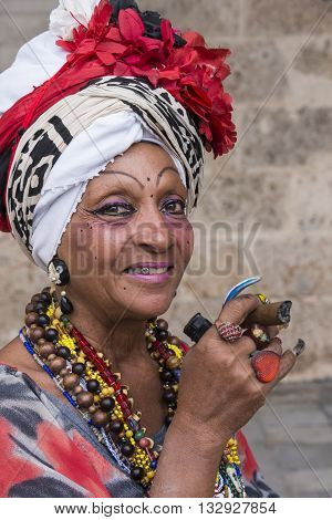 Havana, Cuba - january 19, 2016: Mature woman with typical attire, smoking a cigar in Havana, Cuba