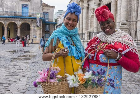 Havana, Cuba - january 19, 2016: Women dressed in traditional costumes and flower baskets in the plaza of the Cathedral of Havana , Cuba