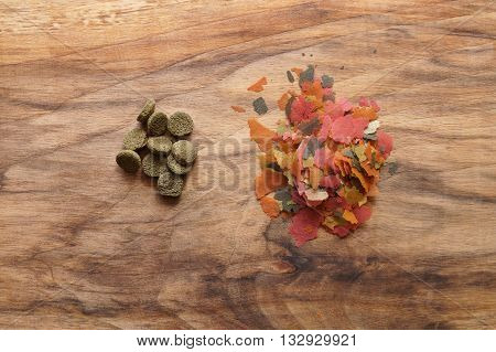 aquarium fish feed flakes and tablets on wooden background