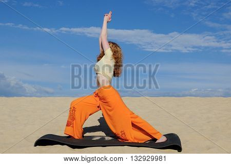 Young slim redhead woman practicing warrior pose from yoga on the beach at sunset. Virabhadrasana 1 pose. On the background of the sand and sky