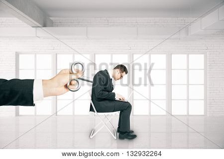 Hand activating businessman with a wind-up key on his back in white brick room. Concept of control
