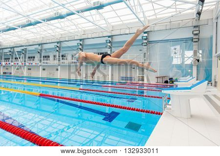 Young muscular swimmer jumping from starting block in a swimming pool.