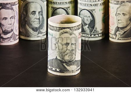 President with ten dollar bills on a background of presidents from other denominations