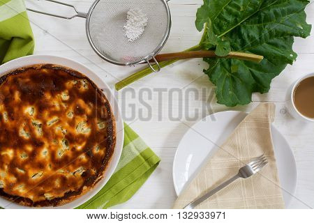 cake or pie rhubarb leaf coffee cup sieve with icing sugar and a plate with napkin on a white painted wooden table view from above