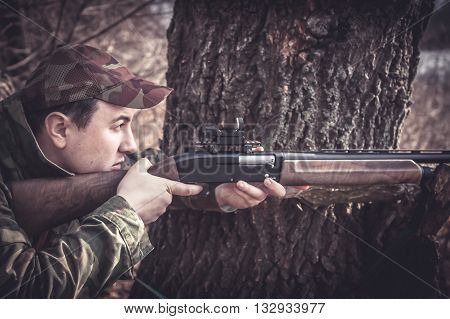 Hunter man with gun aiming and prepared to make a shot during hunting